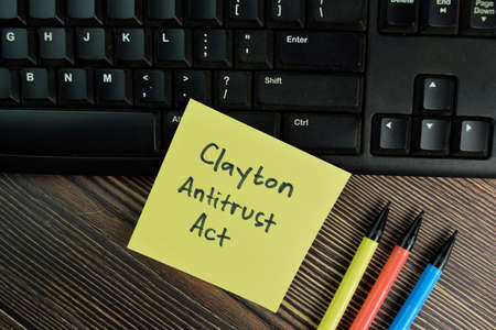 Clayton Antitrust Act write on sticky notes isolated on Wooden Table. 免版税图像