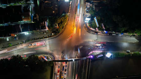 Traffic jam on the polluted streets of Bekasi at night. The traffic congestion is limited in few areas, selective focus on the road. Bekasi, Indonesia, May 8, 2021