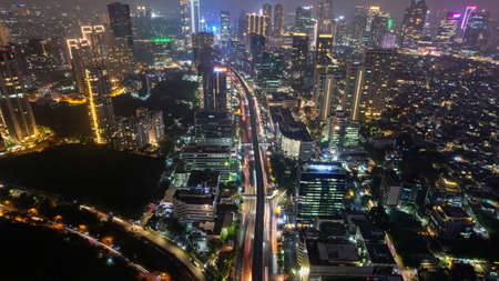 Aerial view of highway intersection and buildings in the city of Jakarta at night and noise cloud with Jakarta cityscape. Jakarta, Indonesia, May 8, 2021 新闻类图片