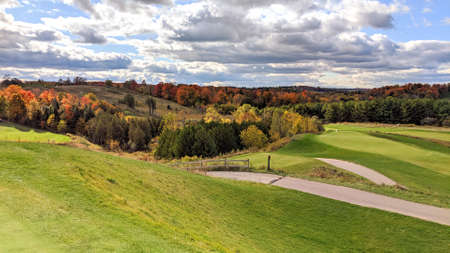 Beautiful golf course scenery on a cloudy autumn day. The cart path is paved around the rolling green hills, the leaves are changing colours, and the plants are swaying with the wind.