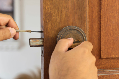 deadbolt: locksmith on wood door for reparing by screwdriver