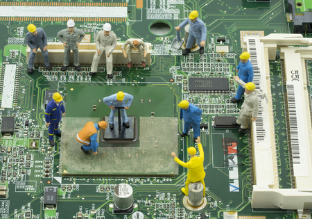 mainboard: mini engineer team to repair chipset on green mainboard - can use to display or montage on product or concept of job response