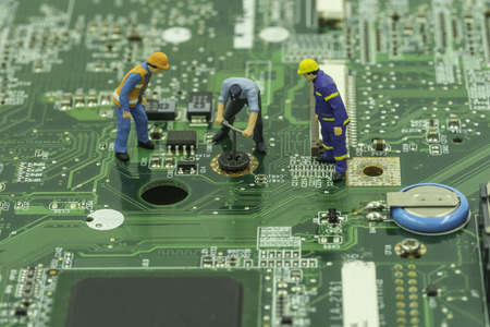 mainboard: mini worker try to remove screw on mainboard with engineer control - can use to display or montage on products Stock Photo