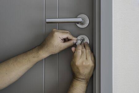cerrajero tratar de abrir la puerta con un destornillador - se puede utilizar para mostrar o montajes en los productos Foto de archivo