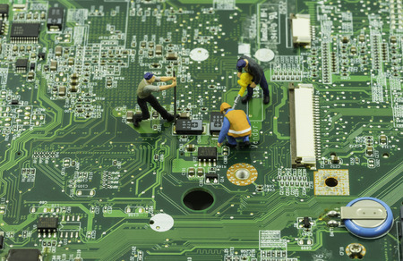 mainboard: mini workers team try to maintain chip on mainboard - can use to display or montage on products Stock Photo