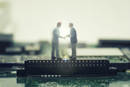 fare: two mini businessman shake hand on stand on mainboard for make a deal on effect light fare - can use to display or montage on products