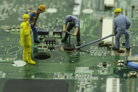 mainboard: mini workers team try to remove screw from green mainboard - can use to display or montage on products Stock Photo