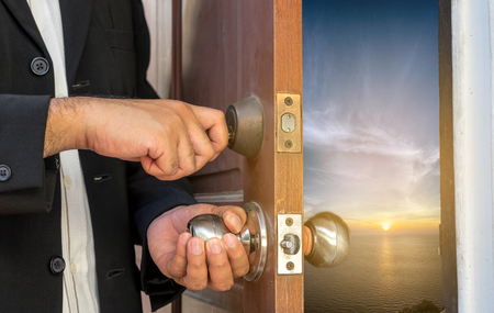 worl: business man in black suit open the door by key  to seascape view can use to display or montage product or concept sea view point