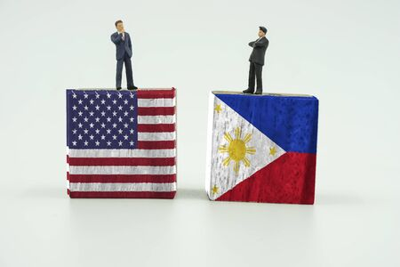 disagree: abstract 2 mini businessman stand on block of USA and Philippines flag on isolate background Stock Photo