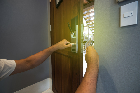 abstract locksmith try to fix smart door handle on wood door - can use to display or montage on product Standard-Bild - 109279323