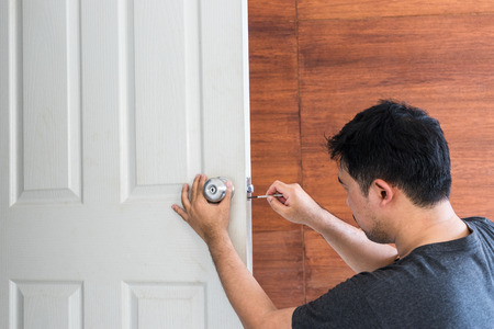 locksmith install and repair knob on white wood door in house - can use to display or montage on product Standard-Bild - 110788774