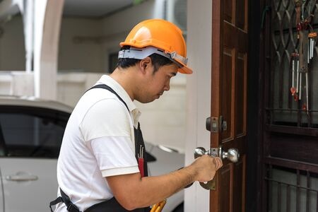 closeup locksmith fix old wood door house , home service of key and lock concept
