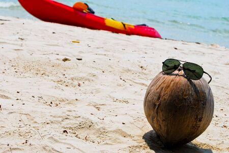 cayak: The sunglass on coconut at beach in thailand Stock Photo