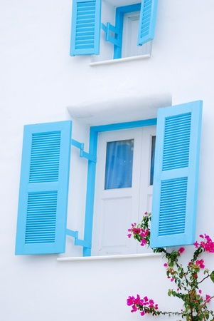 The sky blue windows with flower on white wall photo