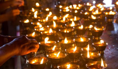 deceased: Woman lighting prayer candle