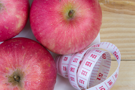 measured: Delicious red apples and measured the meter on wooden background,Healthy food,Diet concept