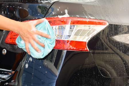 scrub cap: Mans hand washing a soapy black car with a cloth