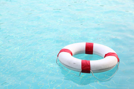 red and white rescue wheel on swimming pool photo