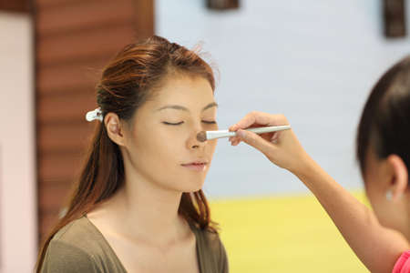 Closeup portrait of a woman having applied makeup by makeup artist photo