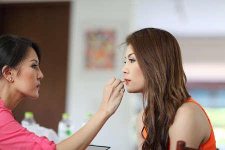 esthetician: Closeup portrait of a woman having applied makeup by makeup artist Stock Photo