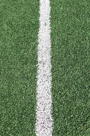 goalline: a green synthetic grass sports field with white line shot from above.  Stock Photo