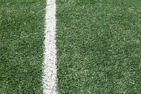 sideline: a green synthetic grass sports field with white line shot from above.  Stock Photo