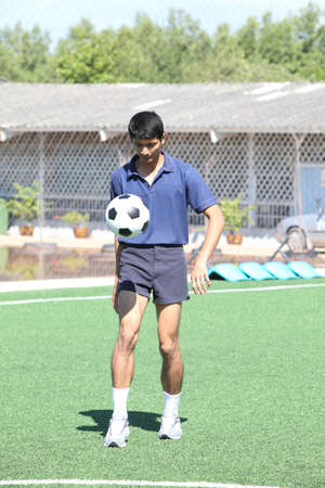 Soccer player juggle the ball  with his feet photo