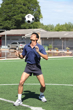 athletic wear: Soccer player juggle the ball  with his head