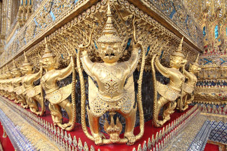 dazzlingly: The statues of Garuda battling naga serpent on the wall of temple in Thailand