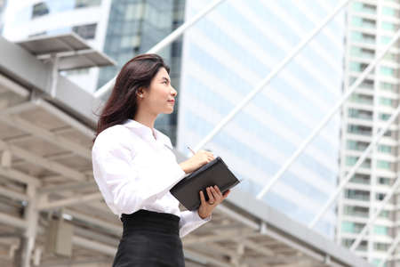 Business woman look something and write massage on her book