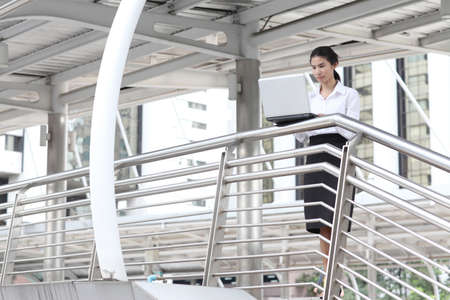 young businesswoman working with her laptop on handrail photo