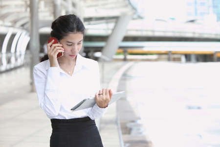 Photo of cute young business woman talking and look at her tablet Stock Photo