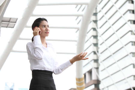 Business woman portrait outdoors talking at the phone with modern building as background Stock Photo