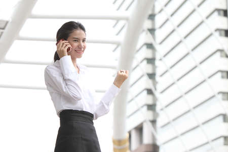 Business lady answering the phone with a smile, receiving good news  photo