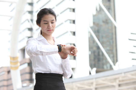 Business woman checking the time with modern building background Stock Photo