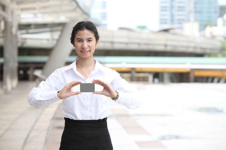 Businesswoman showing and handing a blank business card  photo