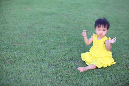 Beautiful little girl playing with grass