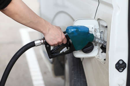 refilling: Close-up of a mans hand refilling a car with a petrolgasoline pump  Stock Photo