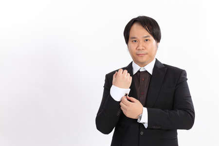 Isolated of business man in suit correcting a sleeve photo
