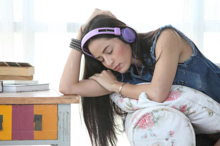 young woman relaxing on an armchair at home, listening to music with a stereo and headphones photo