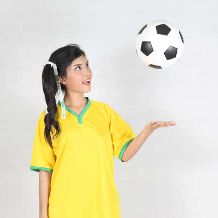 Half Portrait Beautiful woman throw up ball  with wearing Brazil football top photo