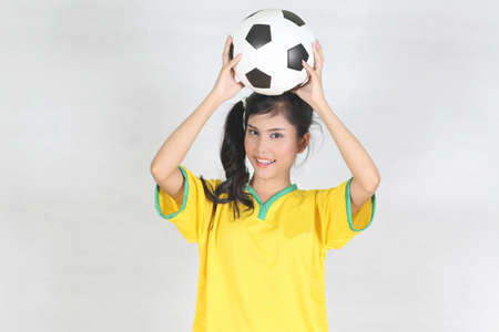 brazil beach swimsuit: Half Portrait Beautiful woman hold ball over her head with wearing Brazil football top