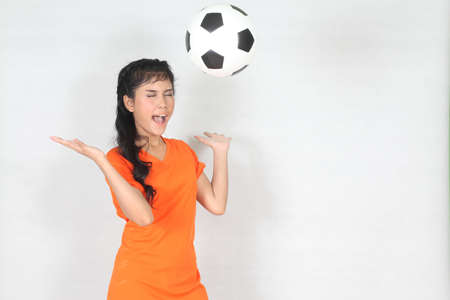 Half Portrait Beautiful woman throw up ball  with wearing football top photo