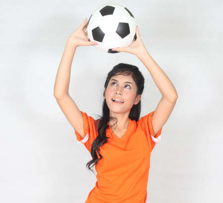 Half Portrait Beautiful woman hold ball over her head with wearing football top