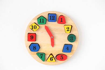 Colorful wooden and any shape clock on the white wall