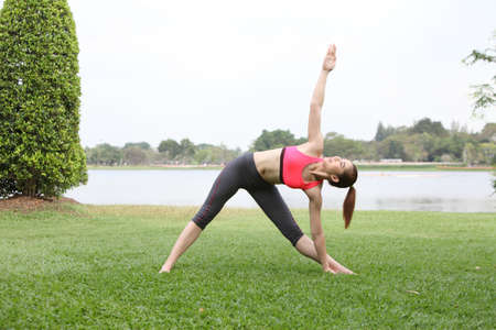 Woman practicing triangle pose outdoors on lawn,right side Stock Photo