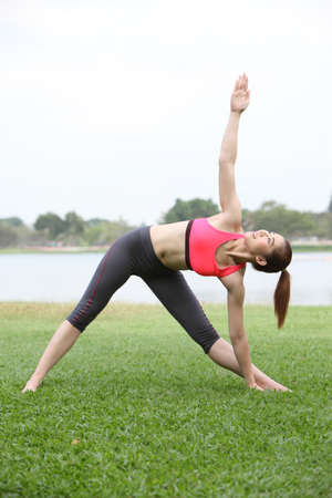 Woman practicing triangle pose outdoors on lawn,right side photo