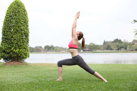 Woman practicing Warrior yoga pose outdoors on lawn,left side photo