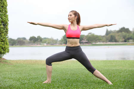 warrior girl: Yoga virabhadrasana II warrior pose by woman on lawn,left side Stock Photo