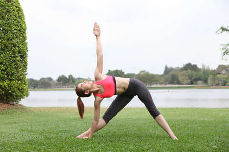 Woman practicing triangle pose outdoors on lawn,left side photo